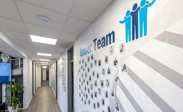 Blick in die Räume der AdWords-Agentur MSO-Digital. Zu sehen ist der Flur, an der Wand sind einige Bilder des Teams zu sehen und Zertifikate zu erahnen.